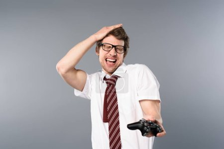 Photo for Excited businessman with closed eyes playing video game with joystick on grey background - Royalty Free Image