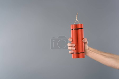Photo for Cropped view of man holding dynamite on grey background - Royalty Free Image