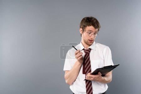 Foto de Hombre sorprendido con lapicero con portapapeles en fondo gris - Imagen libre de derechos