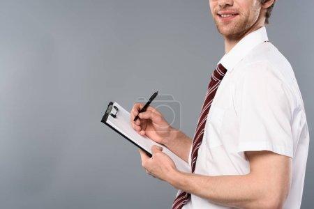 vue recadrée de souriant homme d'affaires avec stylo écriture sur presse-papiers sur fond gris