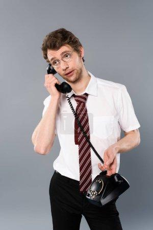 Foto de Empresario adulto en gafas hablando por teléfono vintage aislado en gris - Imagen libre de derechos