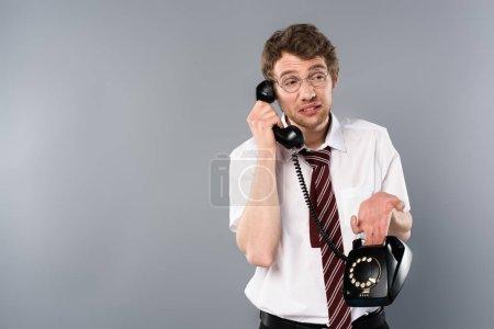Photo pour Homme d'affaires confus dans les verres parler téléphone vintage sur fond gris - image libre de droit
