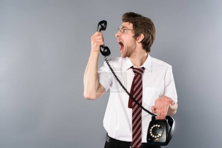 Photo for Angry businessman in glasses yelling in vintage phone - Royalty Free Image