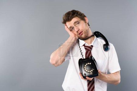 Foto de Empresario agotado en gafas sosteniendo teléfono vintage en fondo gris - Imagen libre de derechos