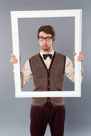 Foto de Hombre gafas guiñando un ojo y celebración de marco blanco sobre fondo gris - Imagen libre de derechos