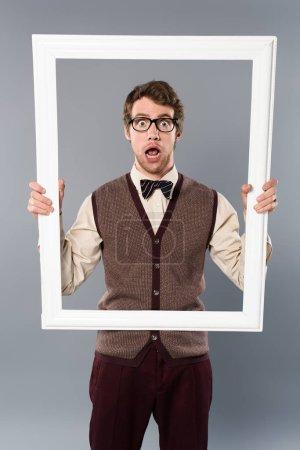 shocked man holding white frame on grey background