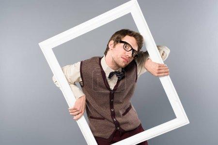 Foto de Hombre divertido con marco blanco sobre fondo gris - Imagen libre de derechos