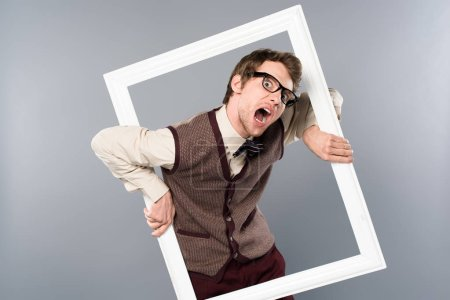 Photo for Funny man screaming and  holding white frame on grey background - Royalty Free Image
