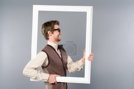 Photo for Side view of smiling man holding white frame on grey background - Royalty Free Image