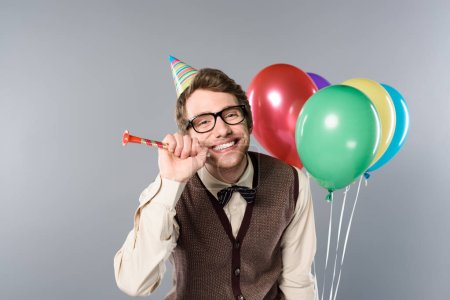 Photo for Smiling man in glasses and party cap holding multicolored balloons and party horn on grey background - Royalty Free Image