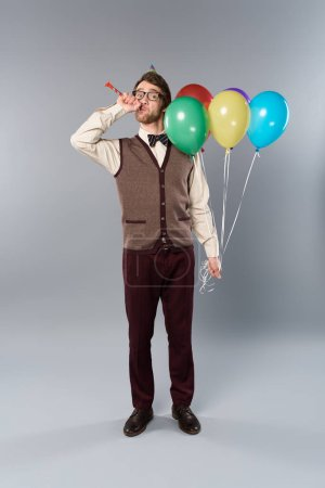 Photo for Man in glasses and party cap holding multicolored balloons and blowing in party horn on grey background - Royalty Free Image