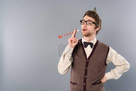 Photo pour Homme drôle dans les verres et cap parti imitation corne parti fumer sur fond gris - image libre de droit