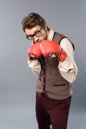 Photo pour Homme sérieux dans les verres et les gants de boxe sur fond gris - image libre de droit
