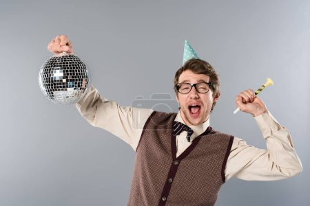 Photo for Excited man in party cap holding shiny disco ball and party horn on grey background - Royalty Free Image