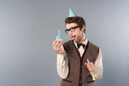Photo for Man in glasses and party cap with funny face expression holding cupcake and party horn - Royalty Free Image