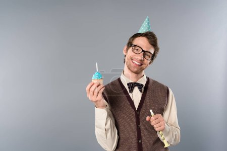 Photo for Smiling man in glasses and party cap holding cupcake with candle - Royalty Free Image