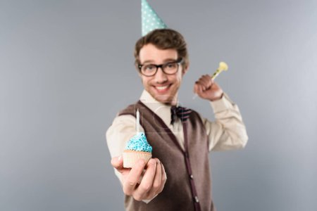 Photo for Selective focus of smiling man in glasses and party cap holding cupcake with candle - Royalty Free Image