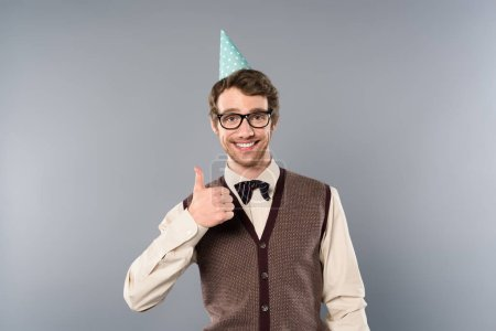 Photo for Smiling man in party cap and glasses showing thumb up - Royalty Free Image