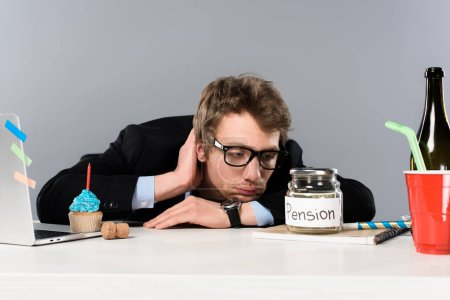 Photo for Sad  businessman in glasses looking at pension moneybox isolated on grey - Royalty Free Image