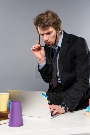 Photo pour Homme d'affaires confus assis au milieu de travail et à l'aide d'ordinateur portable - image libre de droit