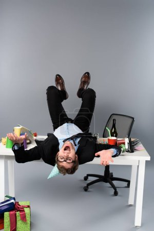 Photo for Happy businessman in party cap lying on table at messy workplace - Royalty Free Image