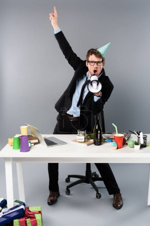 Photo for Excited businessman yelling in loudspeaker at workplace - Royalty Free Image