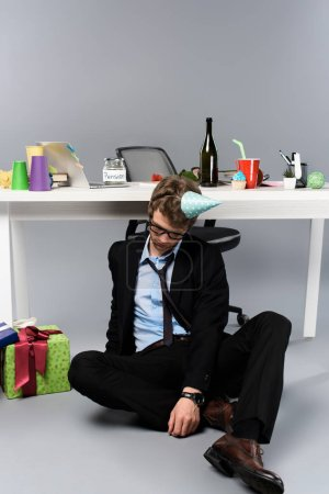 Photo for Drunk businessman in party cap sleeping at messy workplace near presents - Royalty Free Image