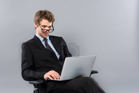 Photo for Businessman in suit and glasses sitting in chair and using laptop on grey background - Royalty Free Image