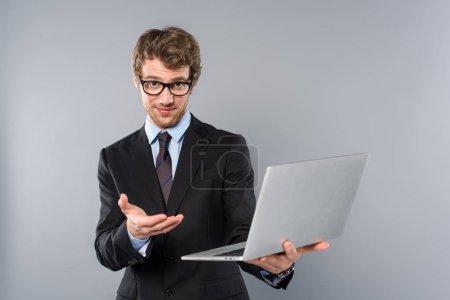 Foto de Hombre de negocios en traje usando laptop y gesticulando sobre fondo gris - Imagen libre de derechos