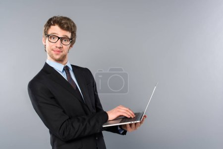 Photo for Funny businessman in suit using laptop on grey background - Royalty Free Image