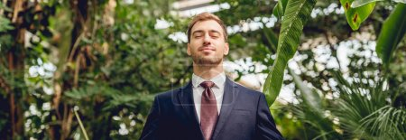 Photo for Panoramic shot of joyful businessman with closed eyes in greenhouse - Royalty Free Image