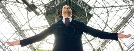 Photo for Panoramic shot of joyful businessman with outstretched hands in greenhouse - Royalty Free Image