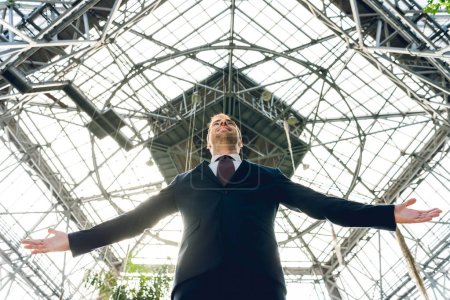 Photo for Low angle view of joyful businessman with outstretched hands in greenhouse - Royalty Free Image