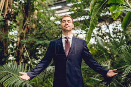 Photo for Joyful businessman with closed eyes and outstretched hands standing in greenhouse - Royalty Free Image