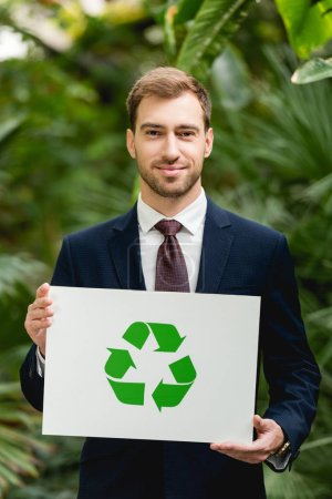 handsome smiling businessman in suit holding card with green recycling sign in greenhouse