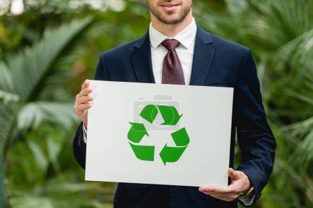 Photo pour Vue recadrée de l'homme d'affaires souriant en costume tenant la carte avec signe de recyclage vert en serre - image libre de droit