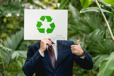 businessman holding white card with green recycling sign in front of face and showing thumb up in greenhouse
