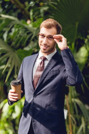 Photo for Smiling businessman in suit, tie and glasses holding coffee to go in orangery - Royalty Free Image