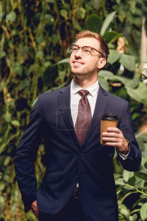 Photo for Smiling businessman in suit, tie and glasses holding coffee to go in greenhouse - Royalty Free Image