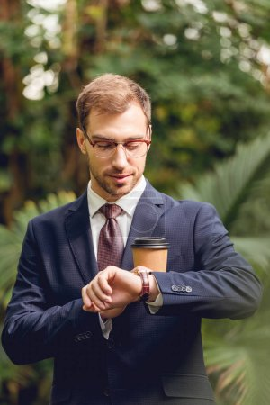 Photo for Smiling businessman in suit, tie and glasses holding coffee to go and looking at wristwatch in greenhouse - Royalty Free Image