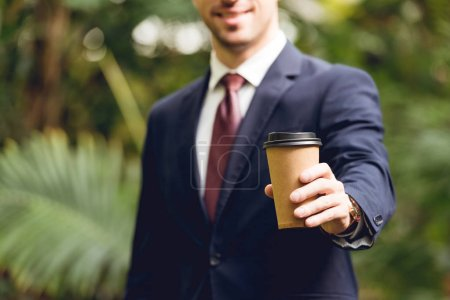 Photo for Cropped view of smiling businessman in suit and tie holding coffee to go in orangery - Royalty Free Image