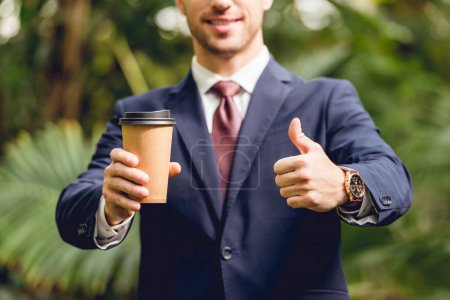 Photo for Cropped view of smiling businessman in suit and tie holding coffee to go and showing thumb up in orangery - Royalty Free Image