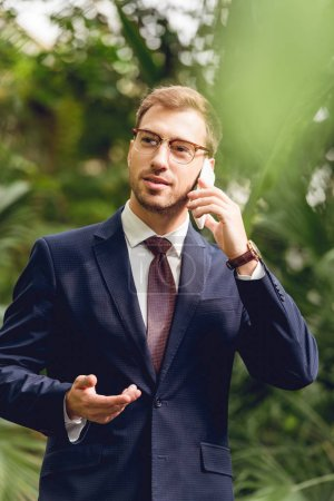Photo for Handsome businessman in suit, tie and glasses talking on smartphone in greenhouse - Royalty Free Image