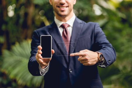Photo for Cropped view of smiling businessman in suit, tie and glasses pointing with finger at smartphone blank screen in greenhouse - Royalty Free Image
