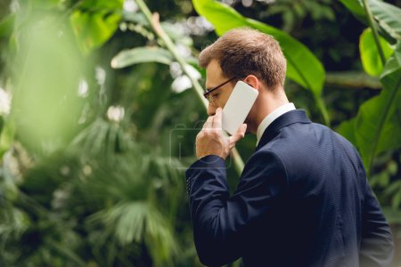 Photo for Businessman in suit and glasses talking on smartphone in greenhouse - Royalty Free Image