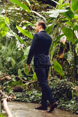 Photo for Happy businessman in suit talking on smartphone while walking in greenhouse - Royalty Free Image