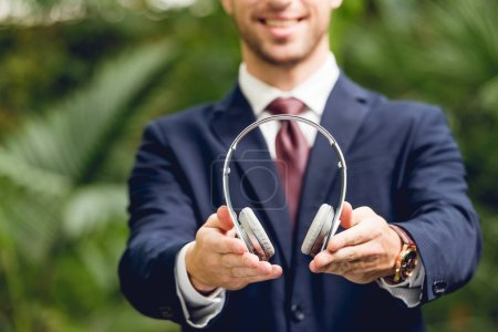 Photo for Partial view of smiling businessman in suit and tie holding wireless headphones in greenhouse - Royalty Free Image