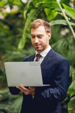 Photo for Smiling businessman in suit and tie using laptop in orangery - Royalty Free Image