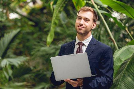 Photo pour Homme d'affaires rêveur souriant en costume et cravate en utilisant un ordinateur portable en orangerie - image libre de droit