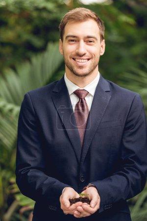 Photo pour Homme d'affaires heureux de sourire dans le procès et la cravate retenant le germe vert et le sol dans des mains dans l'orangerie - image libre de droit